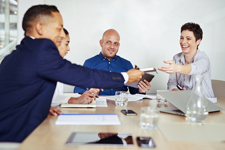 ultrabook: Group of four business executives in the middle of a board meeting in the conference room, everyone looking happy as a mature business woman passes a notebook to her business partner.