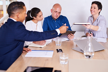 Four business partners together in a conference room with meeting underway as mature caucasian female passed her mixed race business partner seated on the other side of the table.