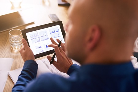 hand held computer: Portable computer tablet being used by a caucasian male business executive during a board meeting to view live analysis of the companys investment portfolio.