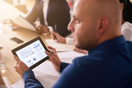 provide: tablet being used in a business meeting with graphs on the display by a caucasian businessman wearing a blue shirt to provide live financial analysis. Stock Photo