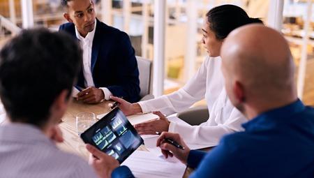 グラフとチャート表示に彼の手で電子タブレットを保持して白人男との営業会議の間に互いに話している 4 つのビジネス人々 のグループ。 写真素材