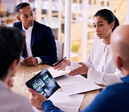 自信を持って若い女性企業経営者忙しい彼のタブレット上の財務グラフを見て 1 つの他のメンバーと会社を展開する彼女の提案のための説明を与え