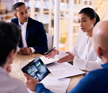 square image of confident young female corporate executive busy giving an explanation for her proposal to expand the firm with one other member looking at financial graphs on his tablet.