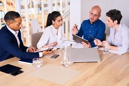 Zakelijke bijeenkomst plaats met diverse groep van mensen uit het bedrijfsleven in een modern kantoor met diverse elektronische apparatuur aan hun hulp, met inbegrip van de tablet wordt gehouden door een van de executives.