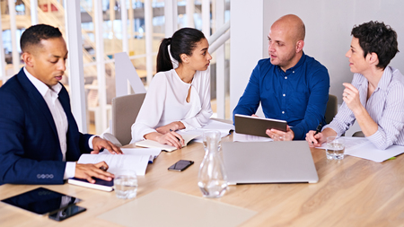 Young diverse and dynamic group of eclectic multiethnic individual business people busy conducting a meeting in a modern office conference room with several electronic devices at their disposal.