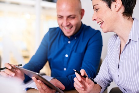 remark: woman making a joke about the status of her company that is being shown to her by her male employee on his tablet while laughing at her remark.