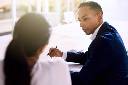 well dressed: Over the shoulder shot of handsome businessman busy talking to his female colleague during their scheduled business meeting, both well dressed individuals of mixed ethnic complexion. Stock Photo