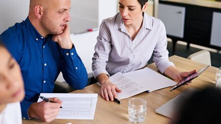 more mature: Mature businesswoman asking her male business colleague for clarification on his work in the companys latest financial reports where she feels more details are required.