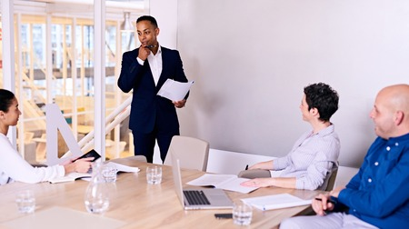 possibly: Businessman standing in front of 3 colleagues in board room busy giving a presentation about their company possibly entering into a collaboration with someone else.