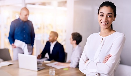 believes: Young multiethnic businesswoman smiling while standing arms crossed in front of the rest of her diverse and dynamic team that she believes in with confidence and can firmly rely on.