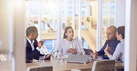 scheduled: Group of four entrepreneurs with dynamic experience and eclectic backgrounds, all busy working together and talking to one and other during a scheduled weekly meeting. Stock Photo
