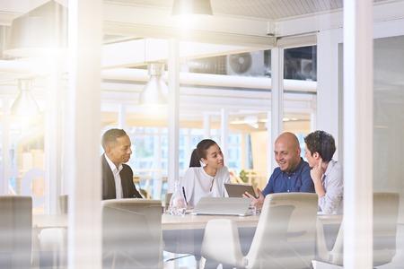 Corporate business meeting in modern office met glazen muren, flare van het zonlicht en reflecties op het glas, terwijl zakelijke discussies plaatsvinden onder bestuursleden. Stockfoto
