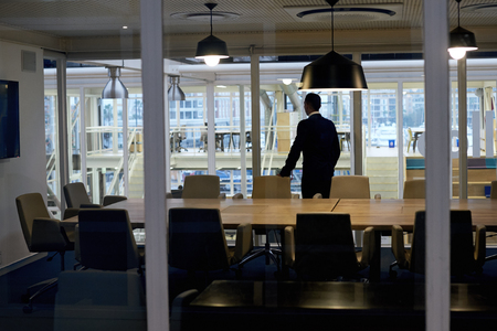 pursue: Successful business man with ambition standing alone in conference room while looking out the window thinking about several business stratergies that he might have to pursue soon. Stock Photo