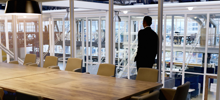 gather: Businessman standing in empty conference room looking out the window, trying to gather his thoughts about possibly having to enter into a merger with his opposition.
