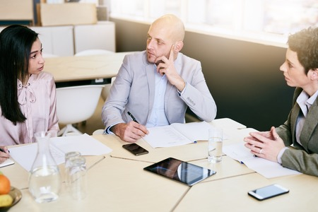 one on one meeting: Business meeting between three executive employees, two female and one male, taking place in a birght conference table early in the morning to prepare for the week ahead.