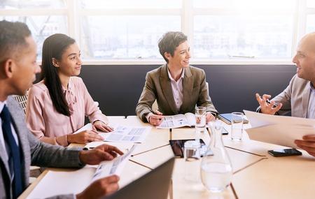 Vier zakenmensen die een vergadering houden in een heldere moderne conferentieruimte met een grote windown en een overvloed aan natuurlijk licht, terwijl ze gebruik maken van technologie om de efficiëntie te optimaliseren. Stockfoto