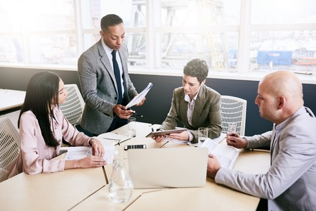 guidance: Professional business manager supervising a business meeting taking place between three of his employees during their early morning meeting in the modern conference room. Stock Photo