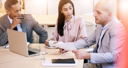 conversing: Three professional business executives conversing with each other during meeting in a bright modern conference room Stock Photo