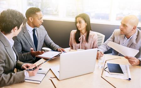 Vier zakenmensen die een vergadering houden in een heldere moderne conferentieruimte met een grote windown en een overvloed aan natuurlijk licht, terwijl ze gebruik maken van technologie om de efficiëntie te optimaliseren.