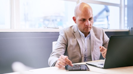 Business man working hard on his notebook and tablet early in the morning in the board room, concentrating and deep in thought while being productive. Stock Photo