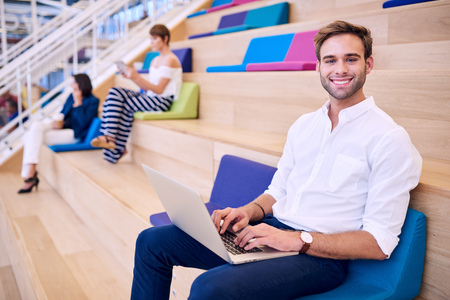 Caucasian man busy using laptop in a public co working space that is bright and colourfull, with two woman out of focus in the background. Stock Photo