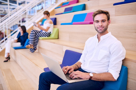 Caucasian man smiling at camera with laptop on his lap, and two well dressed white females in the background behind him in the bright and colourful co working space.