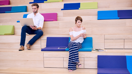 browses: Caucasian man and woman sitting behind one and other on the colourful steps in their local co working space, the woman using her mobile phone while the man browses the internet on his laptop.
