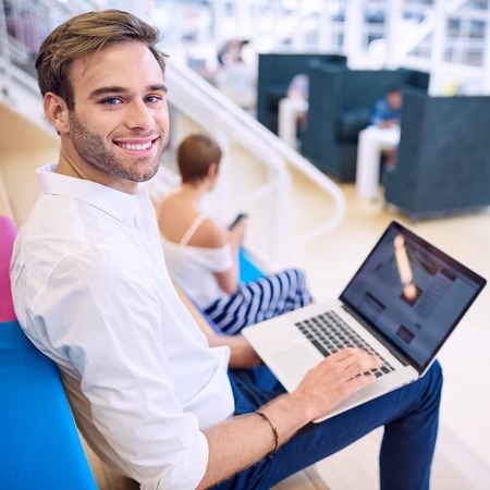 Square shot of handsome man looking at the camera while sitting down on the steps in his co working space with a modern ultrabook on his lap. Stock Photo