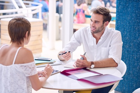 Meeting between successful businesswoman and businessman in public restaurant with the man taking notes from his female business partner, but is looking off camera and smiling candidly. Stock Photo