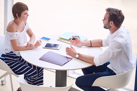 aspirational: Young aspirational female entrepreneur getting professional business advise from a successful business and financial consultant while seated at a round table.