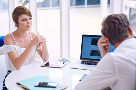 disinterest: Man and woman conducting a business meeting together with lots of technology on the table, but there seems to be a disagreement between them as they show disinterest to one and other. Stock Photo