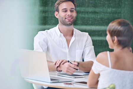 Man playing nervously with his bracelet while interacting with his female colleague during a morning meeting about the upcoming weeks of production that they are busy planning together. Stock Photo