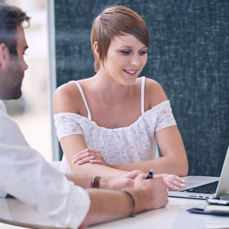 Square image of meeting taking place between male and female business colleagues, as the businesswoman browses the business plan drawn up by the businessman on his ultrabook. Stock Photo