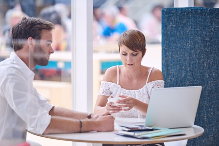 disapproval: Young businesswoman busy messaging on her smartphone during a meeting with her male work colleague, his facial expression showing disapproval of her disinterest. Stock Photo