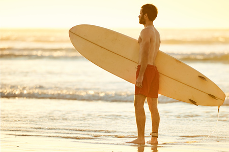 bonne aventure: Young caucasian male wearing red shorts standing in the shallow waves on the beach while holding a surfboard perpendicular to himself. Banque d'images