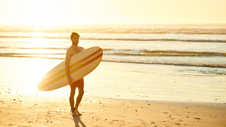 Landscape image of male surfer busy walking on the beach at sunrise while carrying his surfboard under his arm with the ocean waves breaking in the background. Banque d'images
