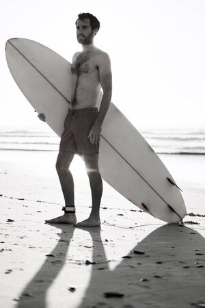 bonne aventure: Black and white image of young male surfer standing on beach with his surfboard under his arm and the waves of the ocean behind him in the background.