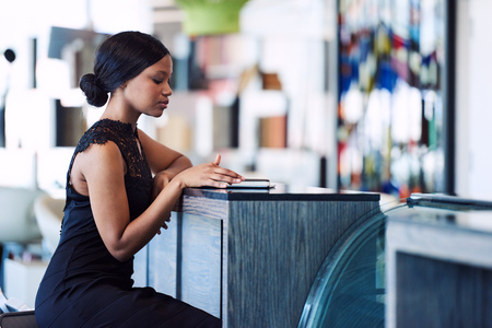 Black woman uisng a digital tablet to catch up on her e-mails while seated alone at a counter in a modern cafe, while wearing a stunning black dress.