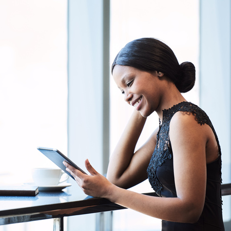 Fashionable and attractive young african woman wearing black busy looking at a digital tablet that she is holding and using on the counter next to a large birhgt window. Reklamní fotografie