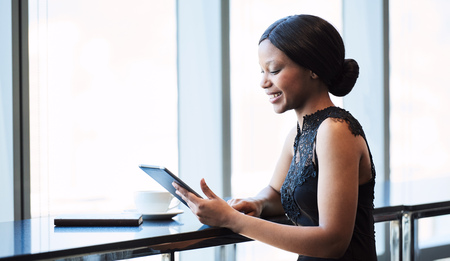 Fashionable and attractive young african woman wearing black busy looking at a digital tablet that she is holding and using on the counter next to a large birhgt window. Stock Photo