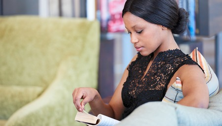 Classy looking black woman sitting on a comfortable couch, still formally dressed from work, but relaxing while reading her favourite novel, about to turn the page. Stock Photo