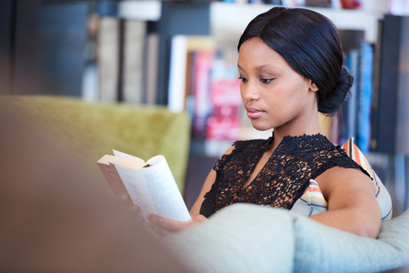 Sophisticated black woman sitting on comfortable sofa while reading her favourite book and relaxing in the comfort of her own home. Stock Photo