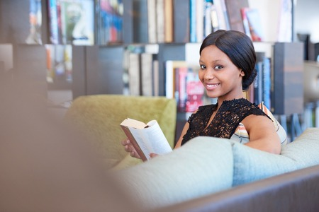 Successful young black woman smiling at the camera while still holding the book she was busy reading seated on the sofa in the comfort of her own home.