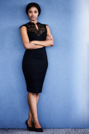Full body image of beautiful young adult black woman looking into camera with serious facial expression, with both her arms and her legs crossed, with a textured blue background.