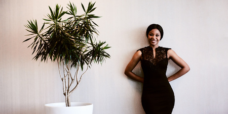 young black woman smiling while looking into camera with her hands behind her back and a pot plant next to her, as she stands against the textured beige wall. Reklamní fotografie