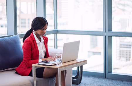 Black businesswoman sitting on a couch in a business lounge while working on her laptop computer with large windows behind her and the cityscape in the distance behind her, while wearing a red blazer.