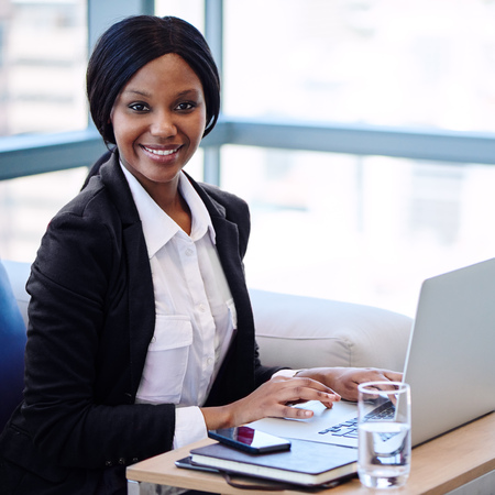 tight square shot of black businesswoman busy smiling while looking at the camera with her hands still on the computer in front of her, staying professional and positive.