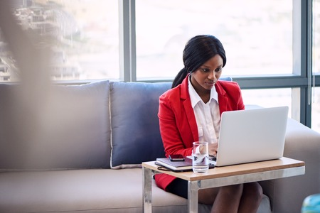 Attractive businesswoman wearing a red blazer busy working on her notebook computer in a business lounge, seated on a blue and grey couch with foreground blur visible in the image. Reklamní fotografie