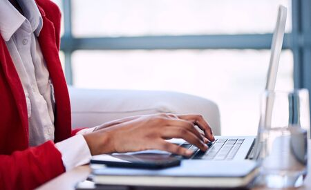 well head: Generic image of a black womans hand busy typing on a modern notebook with her head cropped out of the image while wearing a white shirt and red blazer as well as large windows in the background.