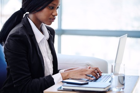 Young adult african business woman wearing a black outfit, busy looking at screen while typing on her notebook, while seted on the sofa in a modern business lounge with large windows. Reklamní fotografie